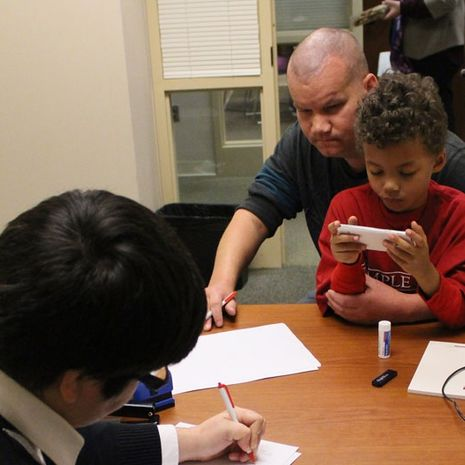 a man looking over forms with attorneys as his young son sits on his lap.