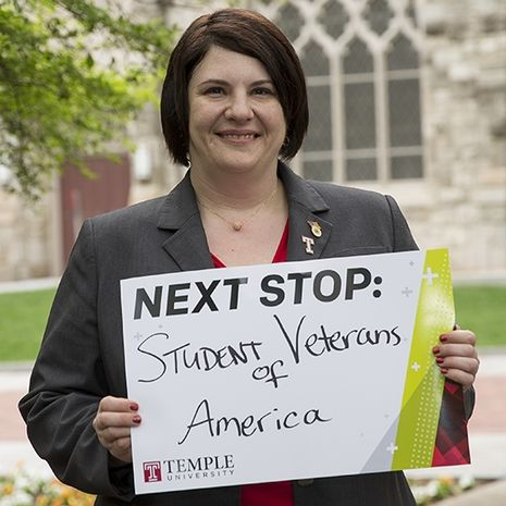 """Tammy Barlet holding a sign that says """"Next stop: Student Veterans of America."""""""