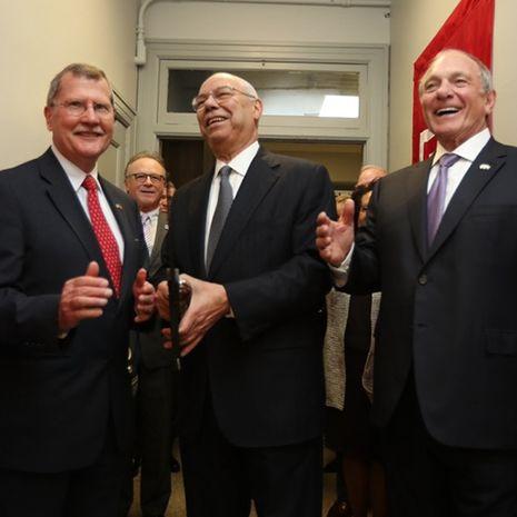 Three men smiling as they cut the ribbon at the veteran center.